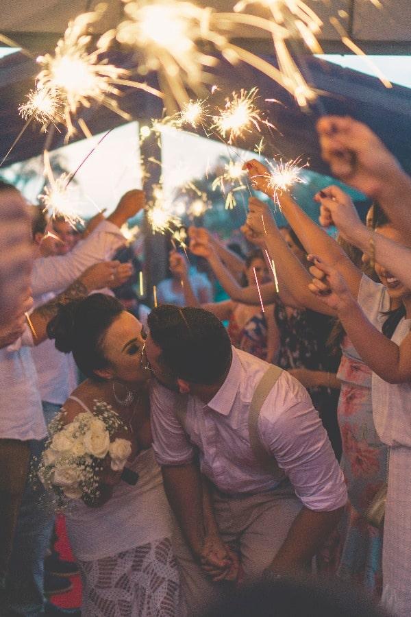 Bride and Groom Kissing Under Sparkling Lights